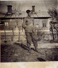 Fotografia żołnierza na tle zabudowy wiejskiej.