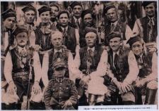 Kresy. Chłopiec w mundurze wojskowym na tle grupy mężczyzn ubranych w stroje ludowe, 1938 r.