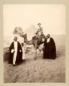 Turysta na wielbłądzie z dwoma Beduinami. W tle piramida i Sfinks